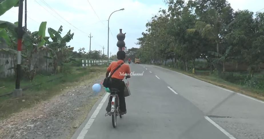 Aksi Unik Lasto, Tukang Pijat yang Selalu Bawa Dua Kendi di Kepala Saat Naik Sepeda - Foto 0